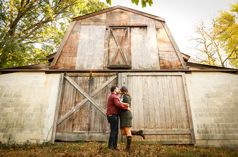 Engagement photography: a couple kisses while standing in front of a large barn. She puts up her foot.