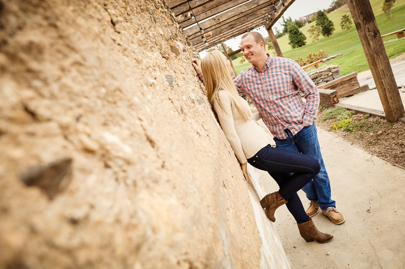 Engagement photography, a couple leans against a wall and smiles at each other.
