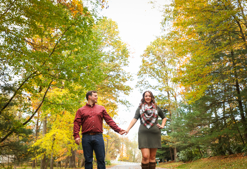 Engagement photography: fall foliage surrounds a young couple holding hands. She wears a green dress and plaid scarf.