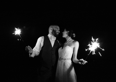 Couple gazing lovingly at each other and holding each other close with sparklers in their hands. Wedding day photo. Black and white filter.