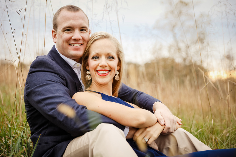Engagement photography, a couple snuggles in the tall grass.