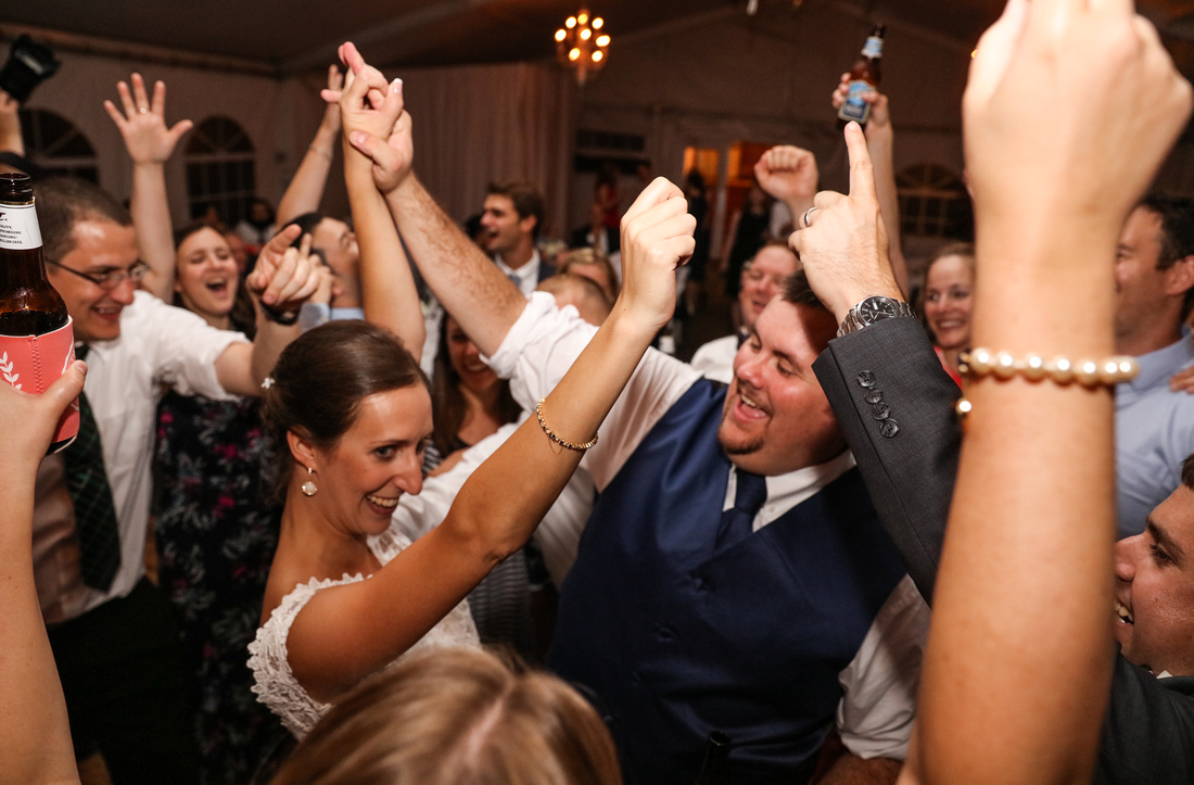 bride and groom in the center of the crowd dancing, arms raised up, smiling and laughing. 2016 in photos