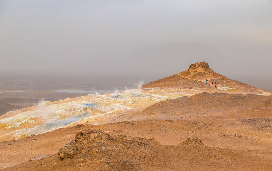 Geothermal steam rises out of the cracks of an orange-brown mountain of iceland. Far in the distance, four hikers walk the trail. 2016 in photos.