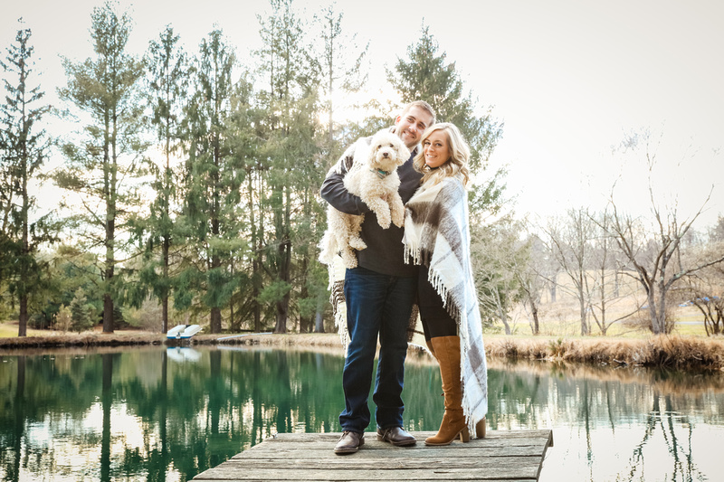 Engagement photography, a couple stands on a dock in front of a pond holding a small white dog.