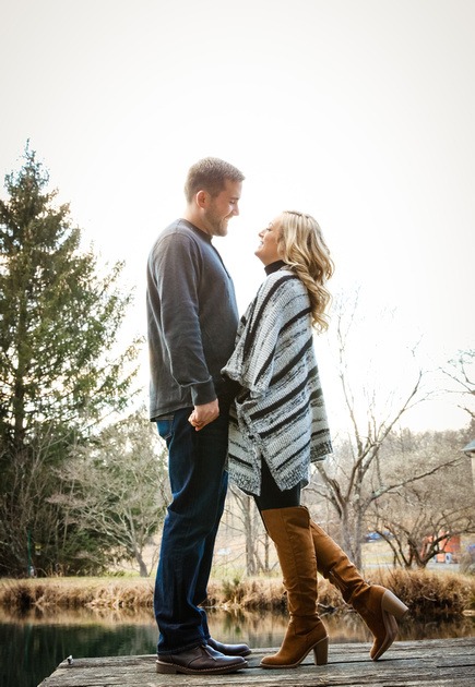 Engagement photography, a blond woman in brown knee-high boots smiles at her fiancé. They stand on a dock.