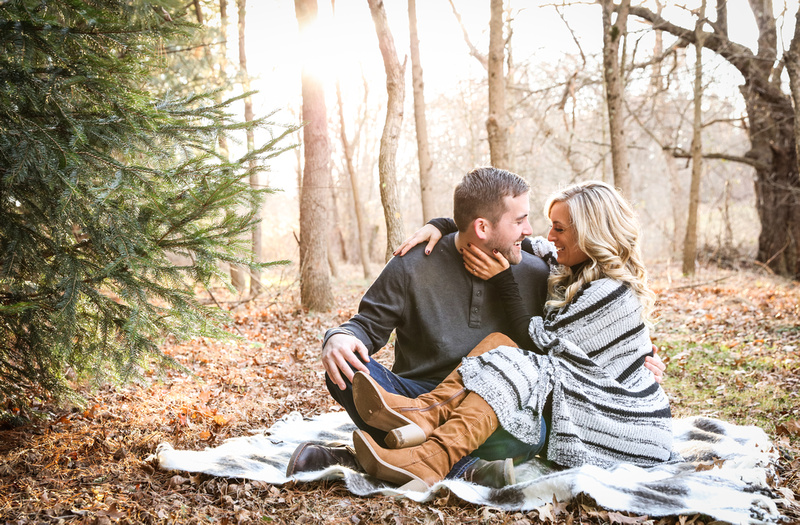 Engagement photography, a couple sits on a blanket in the woods on a sunny winter day. They are laughing.