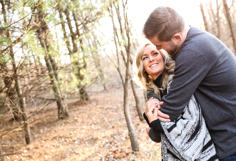 Engagement photography, a couple embraces and gaze into each other's eyes in the woods on a sunny day.