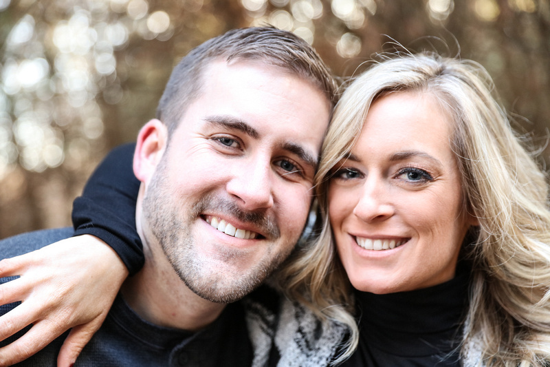 Engagement photography, a close-up shot of two fiancés smiling. She has long blonde hair.