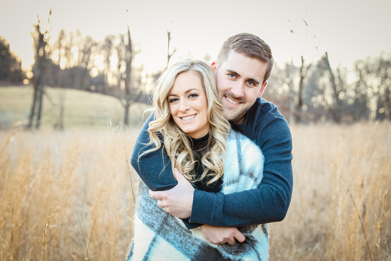 Engagement photography, a man wraps up her fiancé in a grey blanket. They stand in a field.