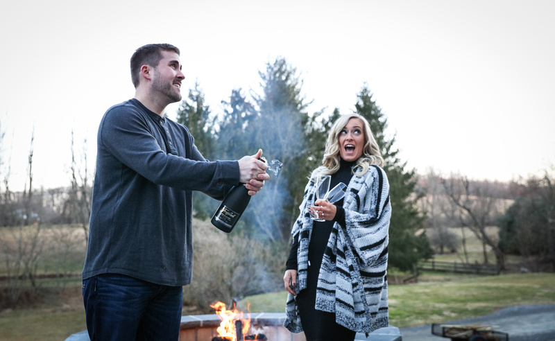 Engagement photography, a couple is surprised as they pop open a bottle of champagne by a fire pit.