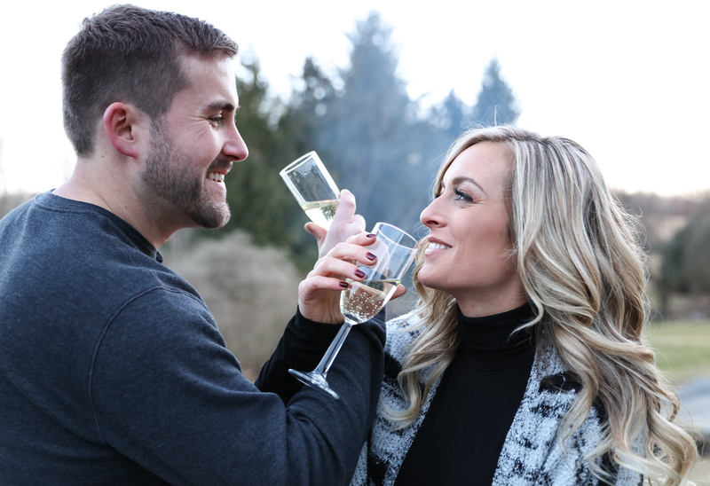 Engagement photography, a couple crosses arms and share a sip of champagne.