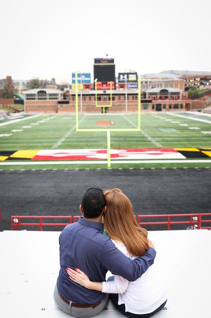 Engagement photography, a couple sits in the bleachers with their arms around each other. He wears a blue shirt.