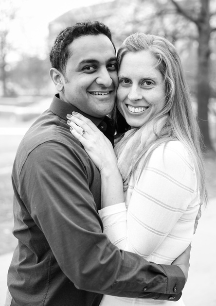 Engagement photography, a couple smiles at the camera with their faces pressed together.