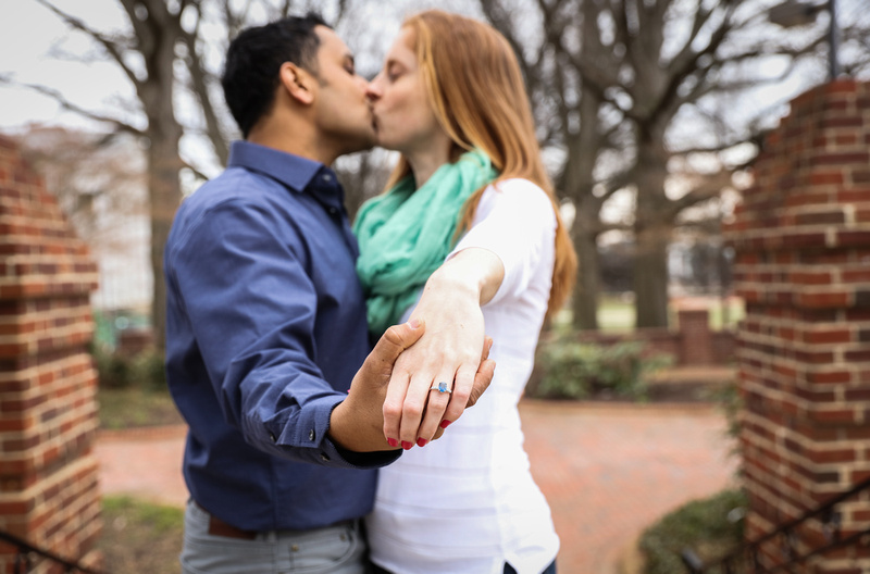 Engagement photography, a couple kisses while holding out their hands. She wears a ring with a blue stone.