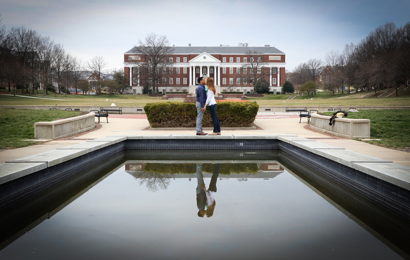 Engagement photography, a couple kisses in front of a reflective pool of water on a school campus.