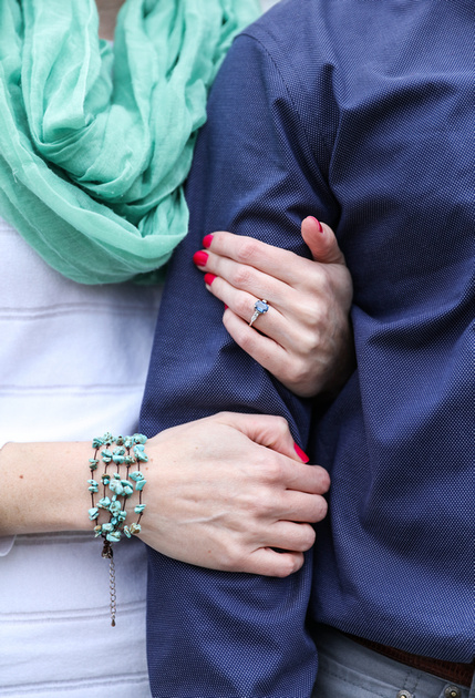 Engagement photography, a closeup of a couple linking arms. She wears a turquoise scarf with a white sweater, he wears a blue shirt.