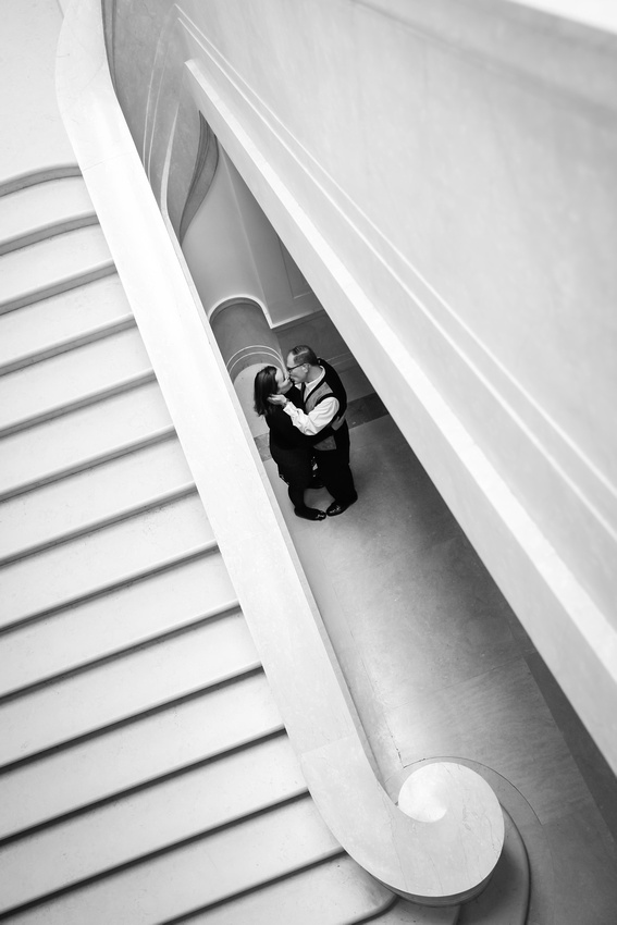 Engagement photography, a couple kisses passionately underneath a grand staircase.
