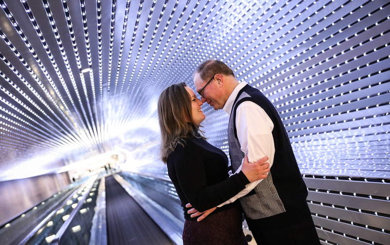 Engagement photography, a couple is nose to nose in a tunnel of lights.