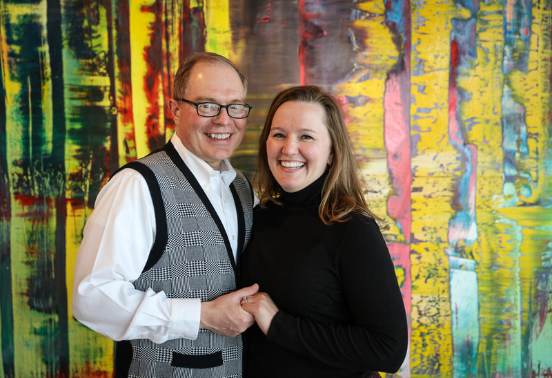 Engagement photography, a couple smiles for the camera while standing in front of a colorful piece of artwork.