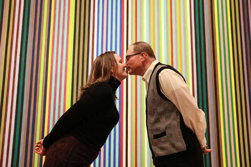 Engagement photography, a couple leans in for a kiss in front of colorful stripes on a canvas.