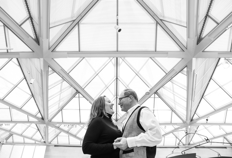Engagement photography, a couple laughs while holding hands. The ceiling behind them is glass with many lines.
