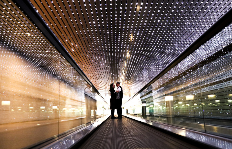 Engagement photography, a couple embraces in a tunnel filled with lights.