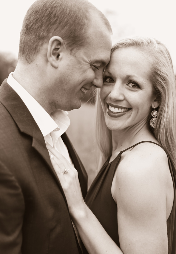 Engagement photography, a young woman smiles at the camera while her fiance closes his eyes and rests his face on hers.
