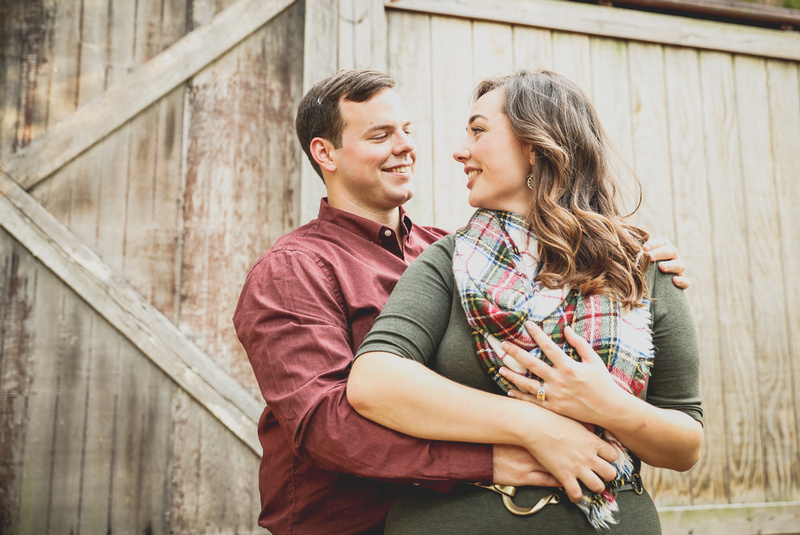 Engagement photography: a young woman in a green dress and plaid scarf smiles at her fiancé.