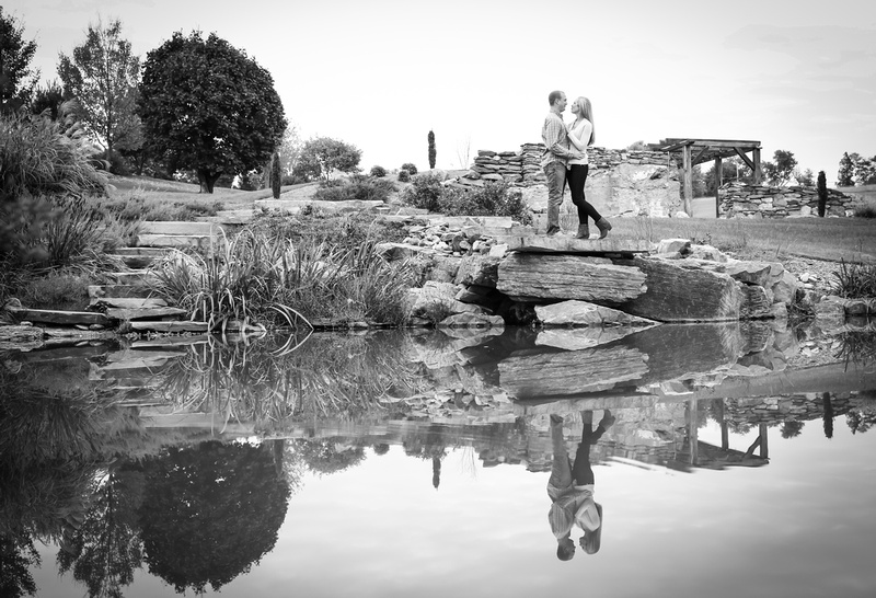 Engagement photography, a couple embraces romantically in front of a still pond.