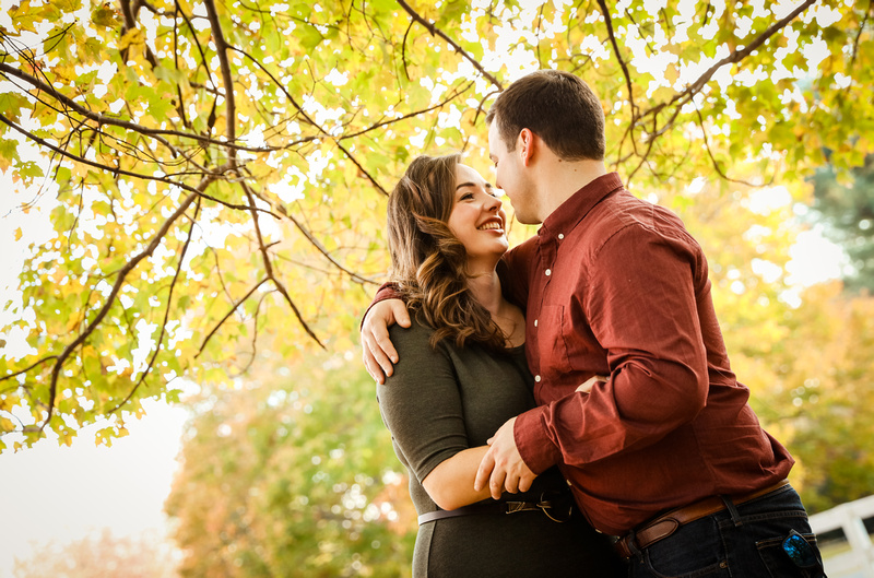 Engagement photography: yellow leaves surround a couple who is embracing.
