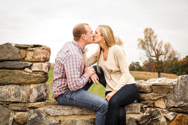 Engagement photography, a couple sneaks a kiss while sitting on a stone wall. They are wearing jeans.