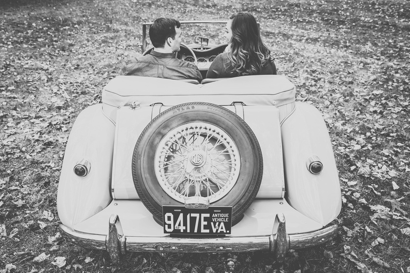 Engagement photography: a young couple sits behind the wheel of an antique car, we see it from behind.