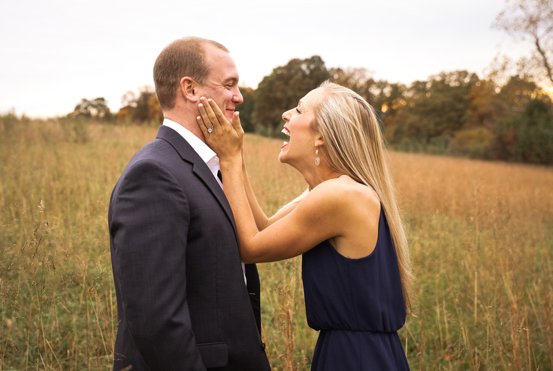 Engagement photography, a young woman in a navy dress holds her fiance's face and laughs.