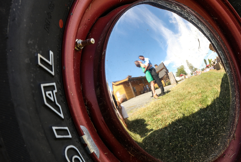 Engagement photography: a photo of a couple's reflection in the wheel of a farm truck. They are embracing.