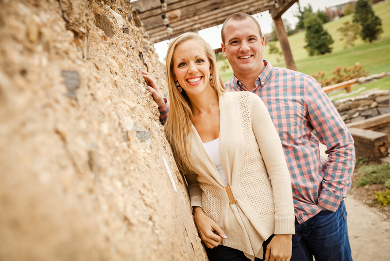 Engagement photography, a couple leans against a stone wall. She wears a cream sweater, he wears a plaid shirt.