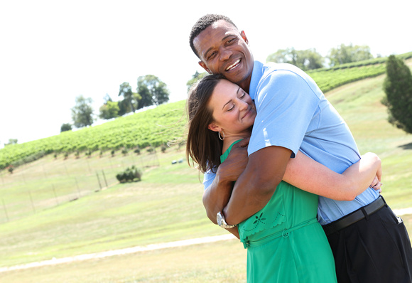 Engagement photography: a man in a blue shirt smiles widely as he hugs his fiancé close. She is wearing a green dress and smiling serenely.