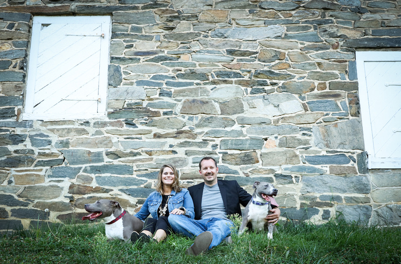 Family photography: A man and woman sit against a stone wall smiling with their two friendly pit bulls.