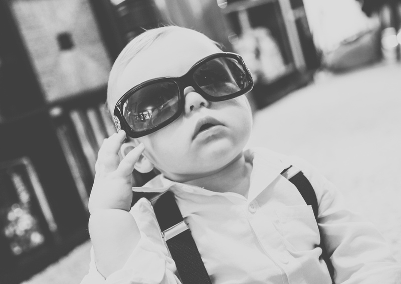 Wedding photography, a baby boy in a white shirt with suspenders is wearing oversized black sunglasses.