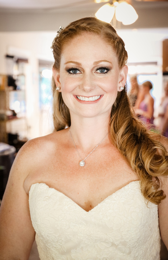 Wedding photography, a smiling bride with long red hair and blue eyes is wearing a sweetheart neckline dress.