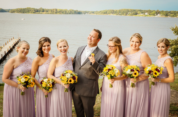 Wedding photography, the groom points to the camera and smiles with the laughing bridesmaids.
