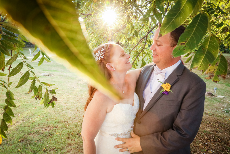 Wedding photography, the bride and groom are nestled under a tree and share a romantic look.