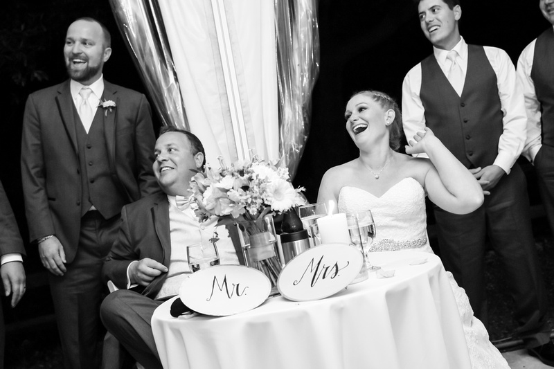 Wedding photography, the bride and groom laugh at their sweetheart table during toasts.