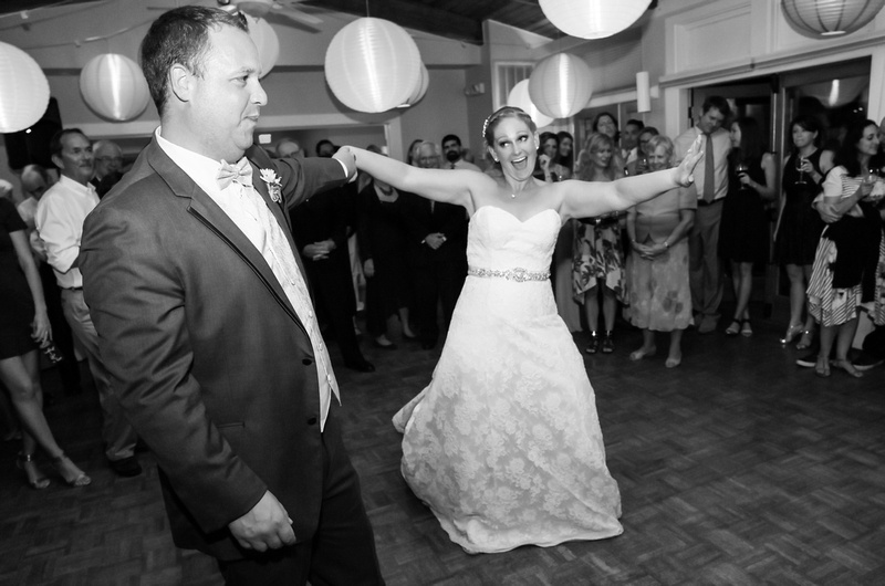 Wedding photography, the bride laughs while dancing with her groom. The ceiling is filled with lanterns.
