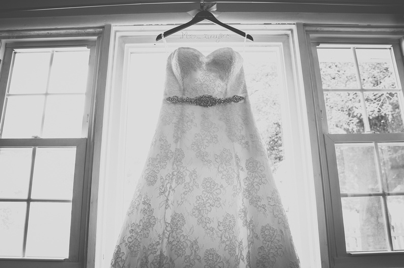 Wedding photography, a white lace gown with beaded embellishments hangs in a picture window.