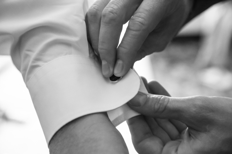 Wedding photography, a close-up of a groom putting on his cuff links.