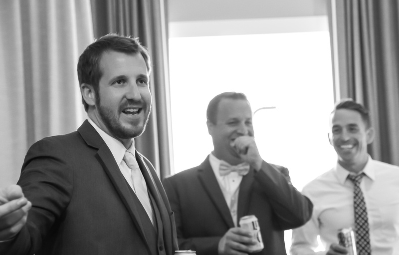Wedding photography, a groom laughs heartily while his groomsman tells a story.