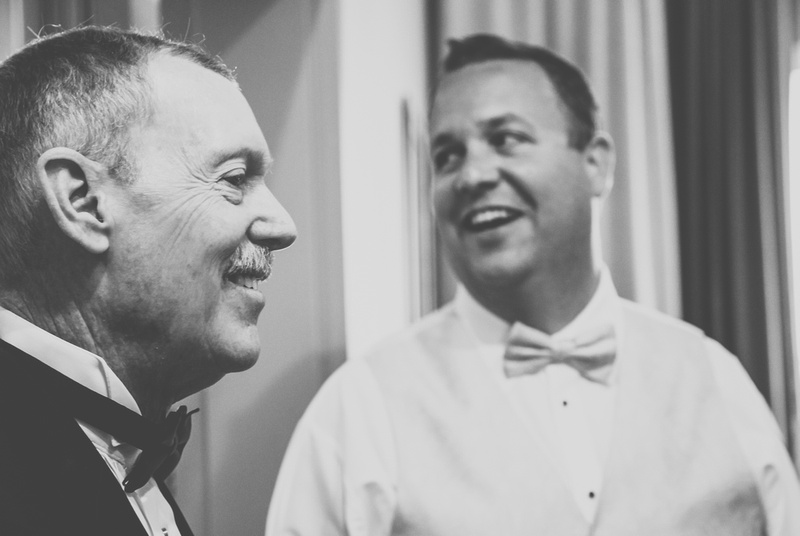 Wedding photography, a groom and his father are smiling. They are both wearing bow ties.