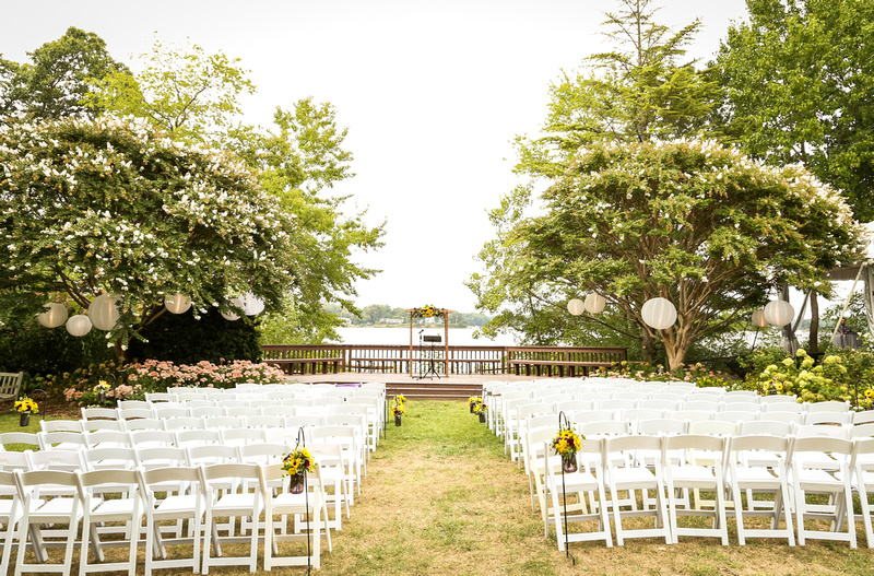 Wedding photography, a waterfront ceremony site is setup with white chairs and lanterns in the trees.