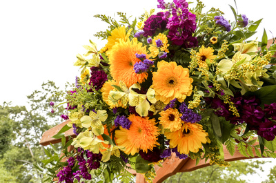 Wedding photography, a bouquet of yellow and purple flowers dons the arbor.