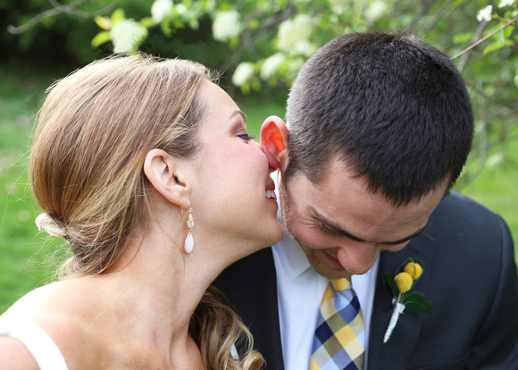 Bride wearing white dangle earrings whispers into the ear of the smiling groom. 5 reasons you need to click with your wedding photographer.